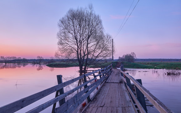Landscape with a wooden village bridge over a spilled spring river in the early morning