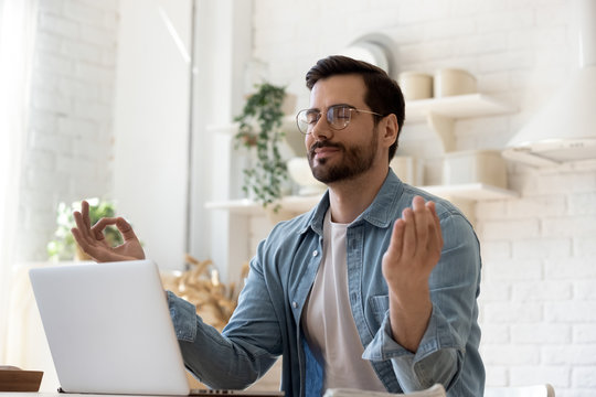 Calm millennial Caucasian man in glasses sit at table distracted from computer work meditate in kitchen, peaceful young male practice yoga relieve negative emotions at workplace, stress free concept