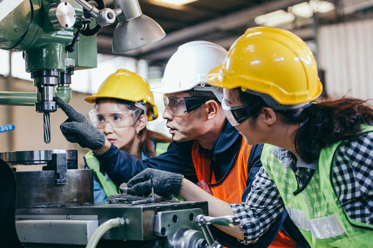 Asian male foreman manager showing case study of factory machine to two engineer trainee young woman in protective uniform. teamwork people training and working in industrial manufacturing business