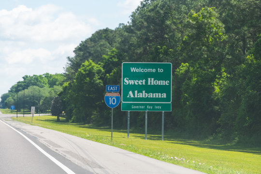 Highway road in Alabama and Mississippi border state welcome sign and text on street on interstate i10 in Grand Bay, AL