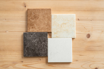 Top-down view of four marble tiles of white, black, light brown and beige colors