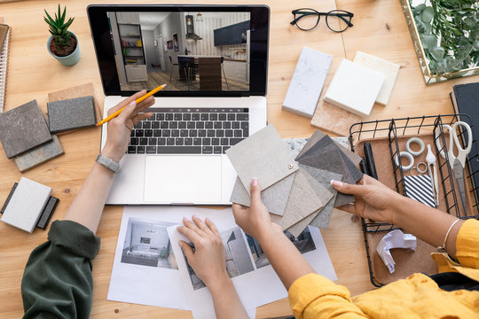 Contemporary designer pointing at home interior example on laptop display