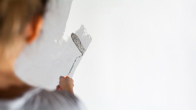 Craftswoman with small paint roller paints white wall with silver-gray paint painting company training teaching profession do it yourself tools