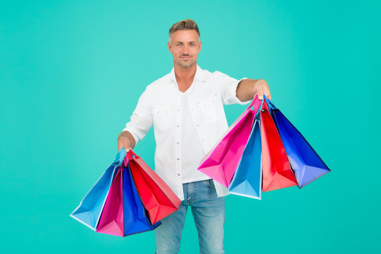 Shop and enjoy. Happy shopper blue background. Handsome man hold shopping bags. Gift shop. Holiday preparation. Souvenir shop. Sale and discount. Shop till you drop