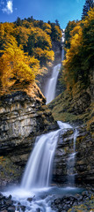 Wall Mural - vertical panorama of the idyllic Diesbach creek waterfall in the Swiss Alps near Braunwald and Glarus in the fall
