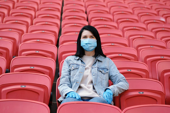 A female fan in a medical mask and rubber gloves sits alone in an empty stadium with red seats. Cancellation of sporting events during the coronavirus. One man army concept.