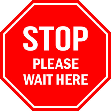 STOP Please wait here sign. Red octagonal background. Social distancing floor sign tells visitors or workers to wait.