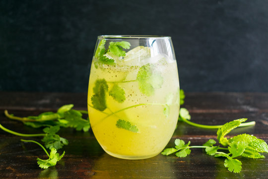 Summer Breeze Cocktail with Garnish: Savory cocktail made with cilantro, cucumber, lime, mint, and prosecco
