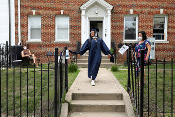 George Washington University graduate Perez struts in her gown during a surprise graduation party by neighbors in Washington