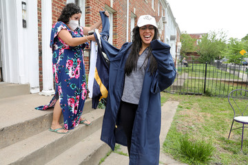 George Washington University graduate Perez laughs as she tries to figure out the sleeves on her gown with the help of her neighbor Drew, at a surprise graduation party in Washington