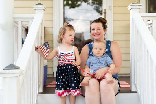 Young mom and two little kids sitting on the front porch on the Fourth of July