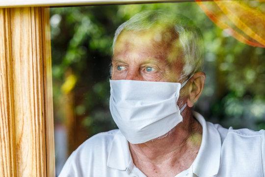 Anziano con mascherina bianca, guarda nostalgico fuori dalla finestra che riflette il verde del giardino