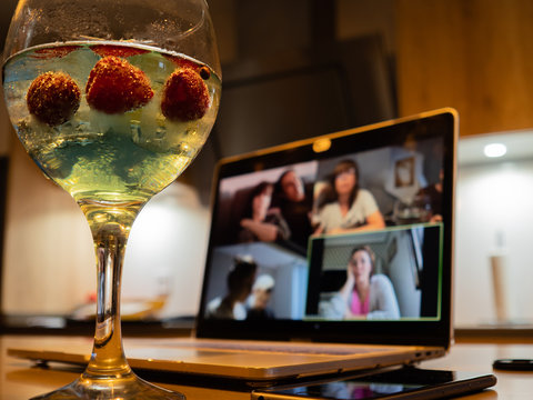 a gin and tonic with strawberries and blue tonic during a video call