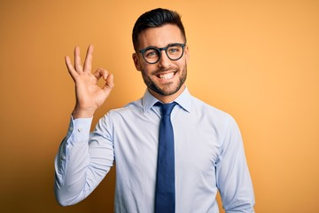 Young handsome businessman wearing tie and glasses standing over yellow background smiling positive doing ok sign with hand and fingers. Successful expression. Fotobehang