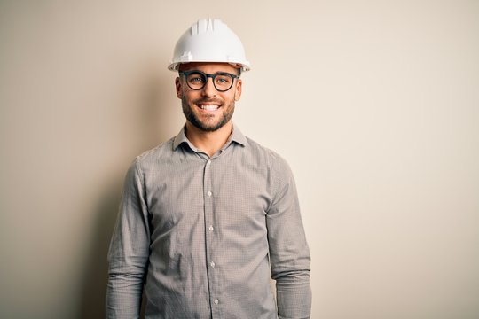 Young architect man wearing builder safety helmet over isolated background with a happy and cool smile on face. Lucky person.