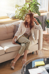 Elegant woman in business attire sitting on sofa with her legs crossed