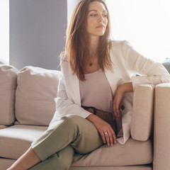 Portrait of young woman in casual business attire sitting on couch.