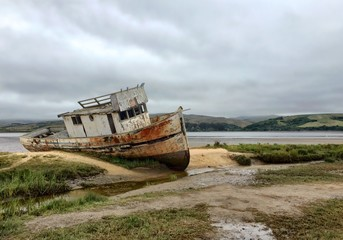 Wall Murals Shipwreck Abandoned Boat By Lake Against Cloudy Sky