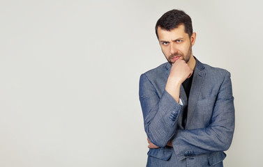 The man is looking thoughtfully at the camera. Confident young man with a beard in a stylish jacket, holds his hand on his chin, raised eyebrow thinks about something makes a plan, ponders a cool idea