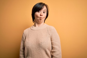 Young down syndrome woman wearing casual sweater over yellow background making fish face with lips,...