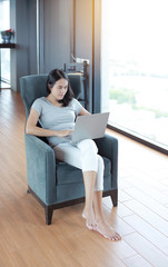 Young asian woman using laptop computer working online at home and feel relaxing. People during the introvert time at home from the epidemic