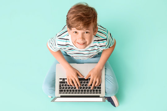 Cute little boy with laptop on color background. Concept of online education