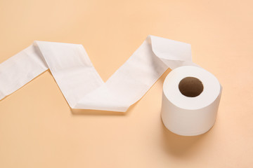 Roll of toilet paper on color background