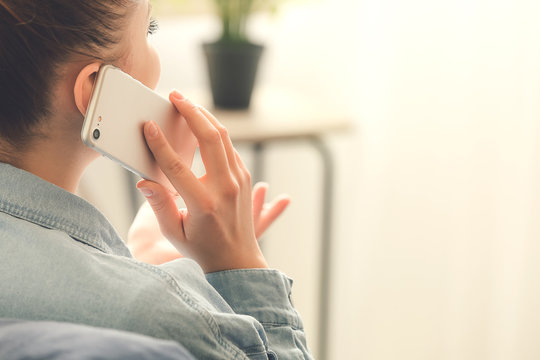 Woman talking by mobile phone at home