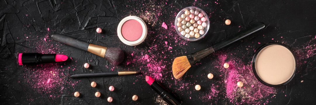 Professional makeup panorama on a dark background. Brushes, lipstick and other products, a flat lay