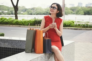 Smiling elegant young woman resting in park after shopping in mall and checking social media on...