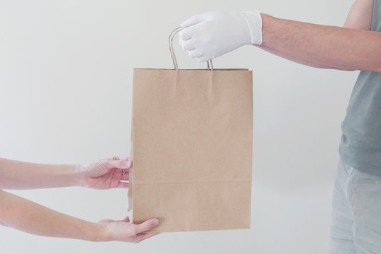 Hand with gloves giving eco paper bag, take away food, home delivery, donation concept