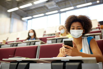 education, healthcare and pandemic concept - african student girl wearing face protective medical...
