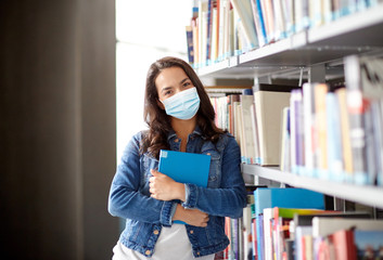 education, healthcare and pandemic concept - student girl wearing face protective medical mask for protection from virus disease with book at library