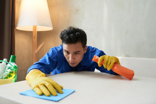 Serious service worker in rubber gloves spraying detergent on table service and wiping it with soft cloth