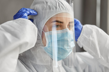 health safety, medicine and pandemic concept - close up of female doctor or scientist in protective wear, medical mask, face shield and gloves for protection from virus disease