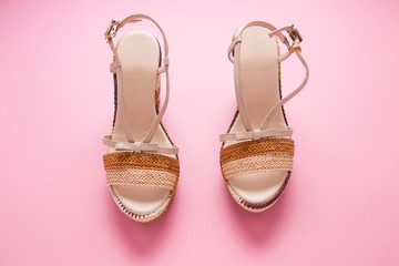 Female summer sandals on a pink background close-up. Wall mural