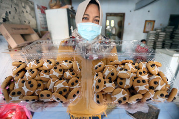 Sulis, 50, shows biscuits depicting emojis wearing protective masks at a cake shop during the outbreak of the coronavirus disease (COVID-19) in Blitar