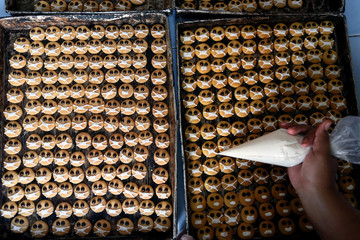Biscuits depicting emojis wearing protective masks are pictured at a cake shop during the outbreak of the coronavirus disease (COVID-19) in Blitar
