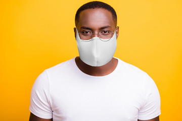 Closeup photo of american man look at camera quarantine social safety epidemic concept wear t-shirt protective respiratory flu facial mask isolated bright yellow background Fotomurales