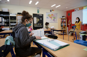 Schoolchildren and a teacher wear protective face masks in a classroom at a francophone primary school as Belgian children head back to their schools with new rules and social distancing in Brussels