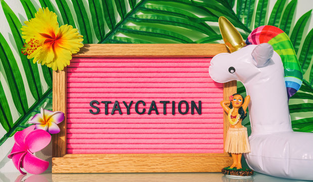 Staycation sign for summer vacation plans during COVID-19. Funny vintage hawaiian pink felt board text for staying home for the holidays. What to do this summer without travel.