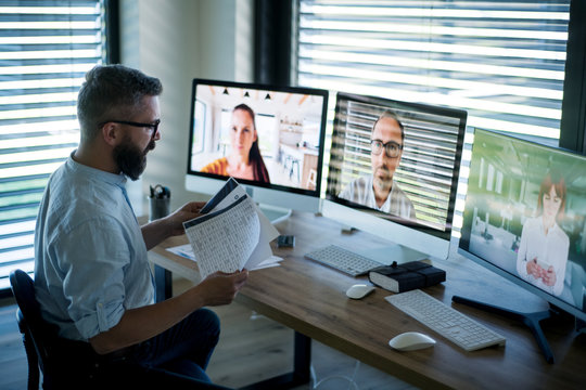 Side view of businessman sitting at desk, having video call.