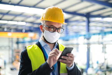 Technician or engineer with protective mask and telephone in industrial factory.
