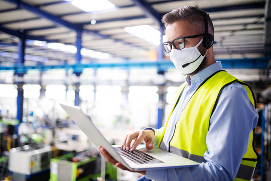 Technician or engineer with protective mask and laptop working in industrial factory.
