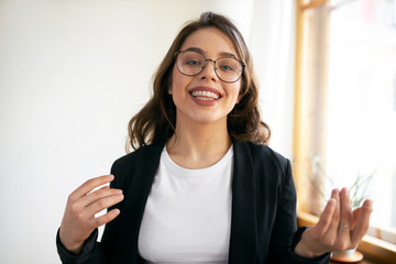 Indoor shot of friendly confident millennial female vlogger in stylish round eyeglasses speaking at...