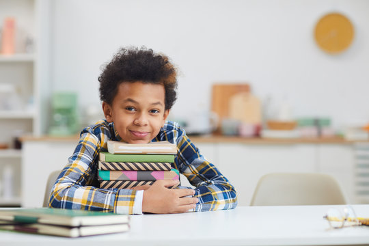 Portrait of cute African-American boy holding stack of books while sitting at desk at home and smiling at camera, copy space