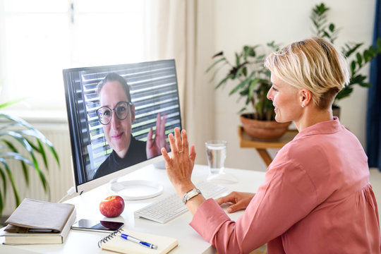 Young businesswoman having video call on computer in home office.