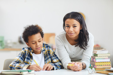 Portrait of young African-American woman smiling at camera while helping son studying at home, copy space