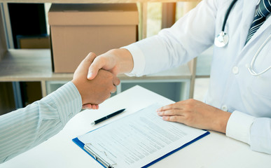 Doctor shaking hands with older patient in the clinic room.