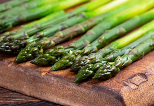 Blanched fresh organic green asparagus on old wooden cutting board